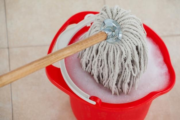 Balde com água espumosa e esfregar o chão de ladrilhos