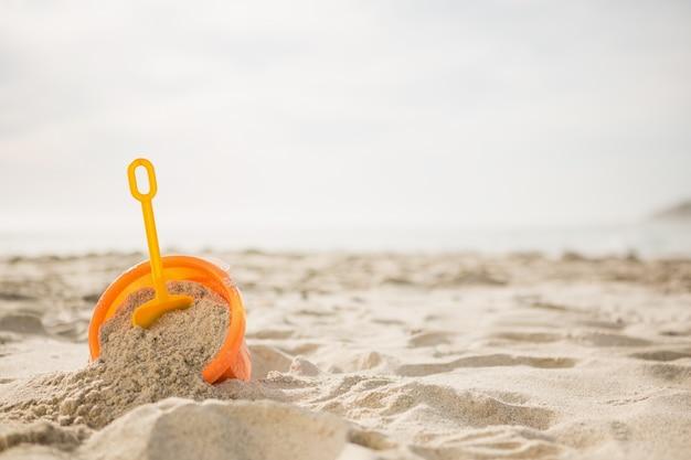 Balde com areia e uma pá na praia