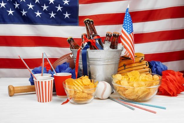 Balde com garrafas de cerveja, batatas fritas e equipamentos esportivos na mesa de madeira branca