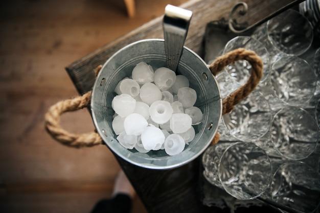 Balde com gelo fica em cima da mesa perto dos copos