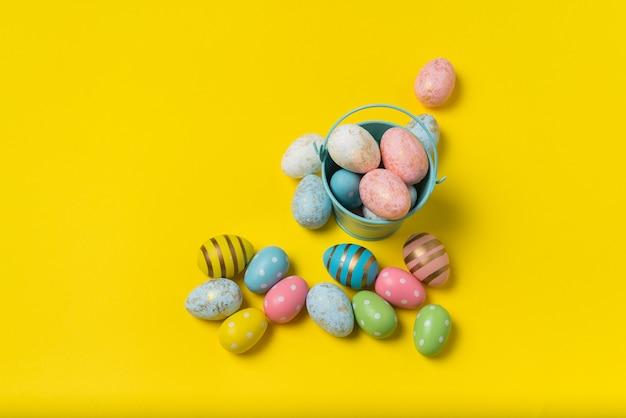 Balde com ovos de páscoa coloridos sobre fundo amarelo brilhante. muitos ovos festivos multicoloridos