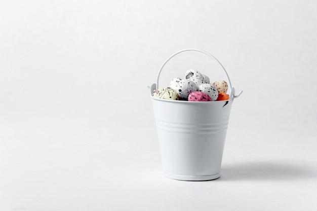Balde com ovos de páscoa em fundo branco. criativo . conceito de minimalismo. copie o espaço para o seu texto.