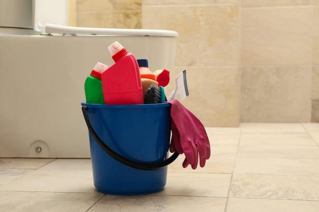 Balde com produtos de limpeza em banheiro moderno