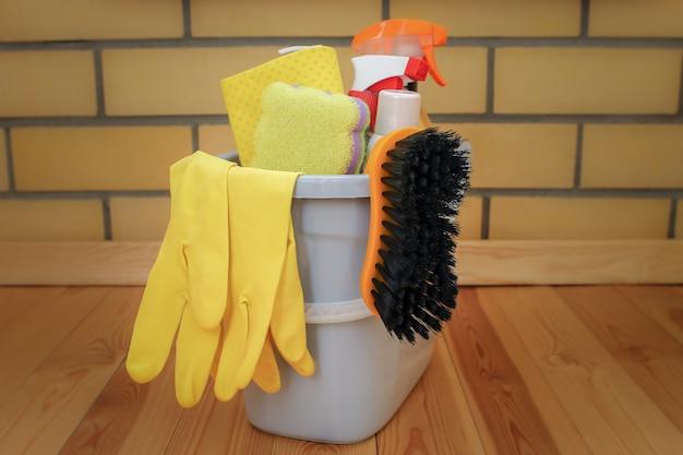 Balde com produtos de limpeza em um piso de madeira. lave e luvas com uma esponja no balde de plástico