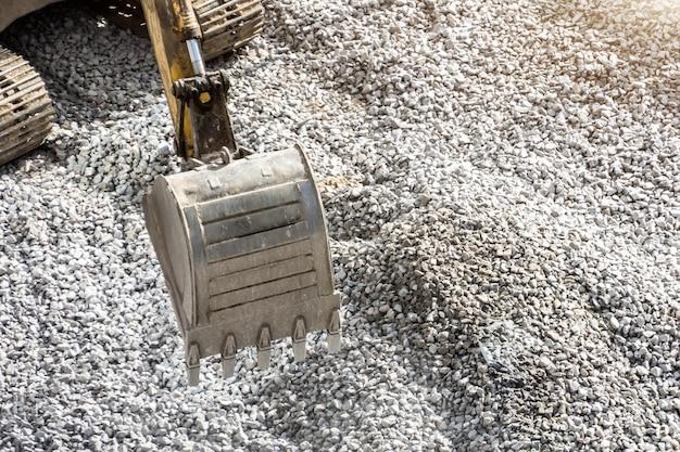 Balde da escavadeira fechar contra um fundo de pedra cinza esmagada.