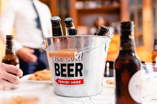 Balde de alumínio com garrafas de cerveja fresca em uma festa.