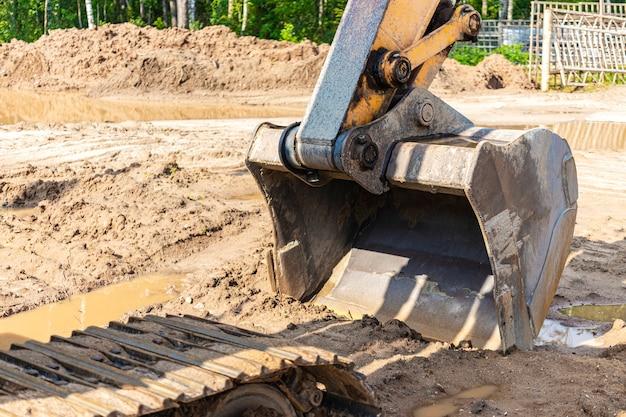 Balde de escavadeira close-up. trabalhos de escavação no canteiro de obras e construção de estradas. maquinaria de construção.
