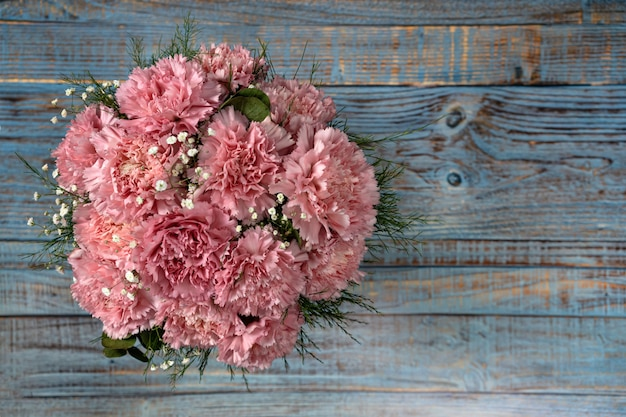 Balde de flores cravo rosa sobre fundo azul de madeira