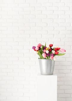 Balde de flores frescas de tulipa sobre fundo de parede de tijolo branco Foto Premium