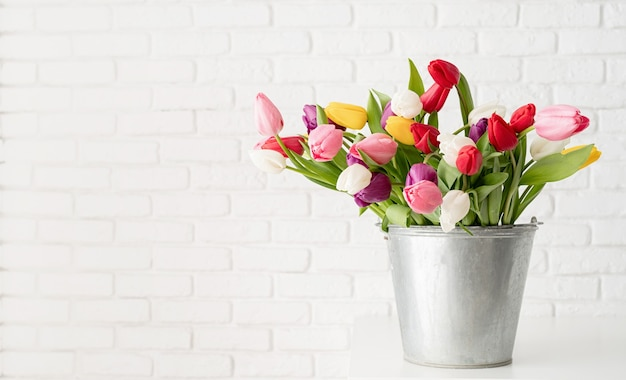 Balde de flores frescas de tulipa sobre fundo de parede de tijolo branco