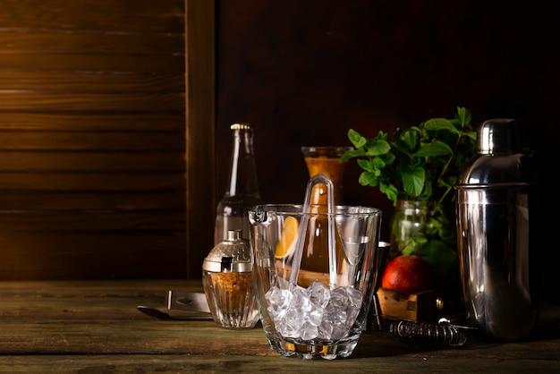 Balde de gelo de vidro e diferentes cocktails em vidro com acessórios bar isolados no preto