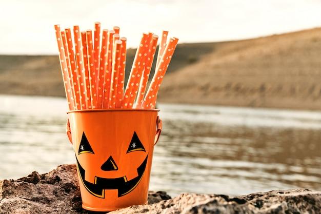 Balde de halloween alegre com canudos laranja