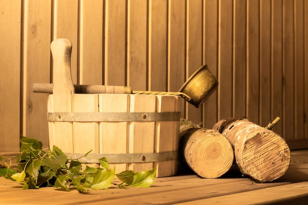 Balde de madeira, vassoura de bétula, lenha e concha na sauna a vapor