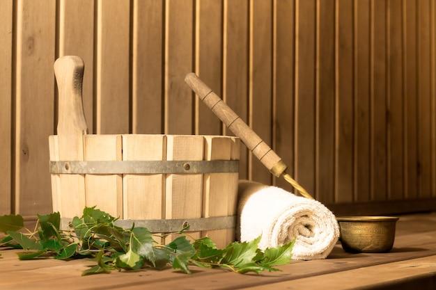 Balde de madeira, vassoura de bétula, toalha e concha na sala de vapor da sauna