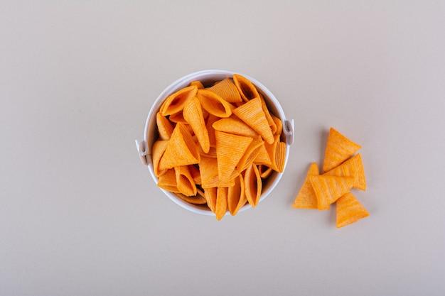 Balde de metal de chips de triângulo em fundo branco. foto de alta qualidade