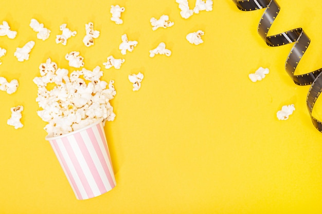 Balde de pipoca e tira de filme sobre fundo amarelo. fundo de filme ou tv. vista superior espaço de cópia