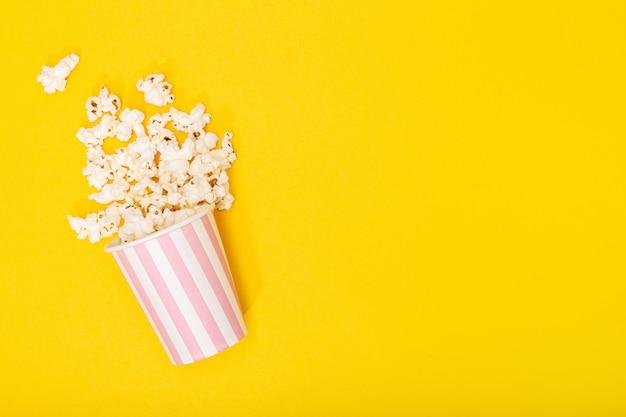 Balde de pipoca em fundo amarelo. fundo de filme ou tv. vista superior espaço de cópia