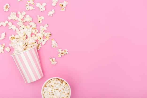 Balde de pipoca em fundo rosa. fundo de filme ou tv. vista superior espaço de cópia