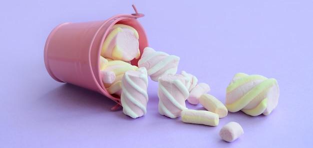 Balde de rosa invertido em miniatura cheio de mentiras de marshmallow