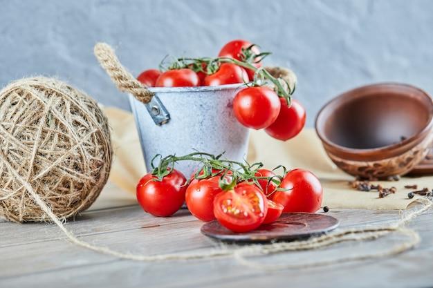 Balde de tomates e metade do tomate cortado na mesa de madeira.
