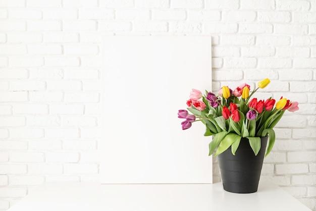 Balde de tulipas no fundo da parede de tijolo branco