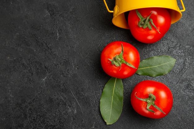 Balde de vista de cima com tomates vermelhos na mesa escura com espaço de cópia