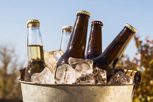 Balde de vista frontal com cubos de gelo frio e garrafas de cerveja