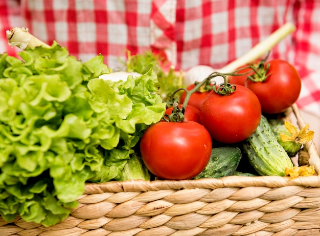 Balde de vista frontal com tomates e pepinos
