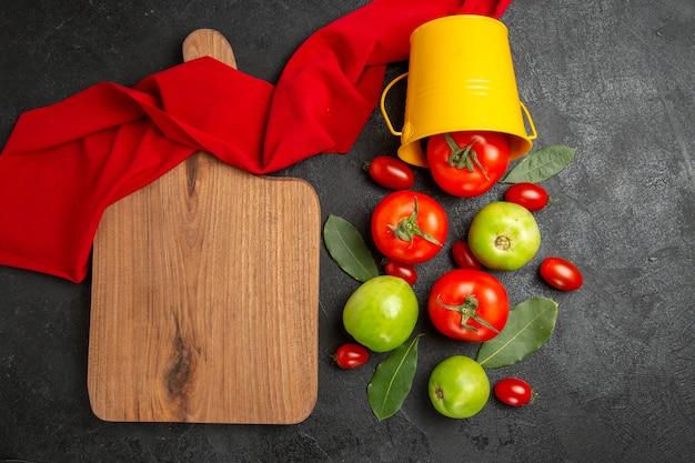 Balde de vista superior com folhas de louro vermelhas verdes e tomates cereja, toalha vermelha e uma tábua de cortar em fundo escuro