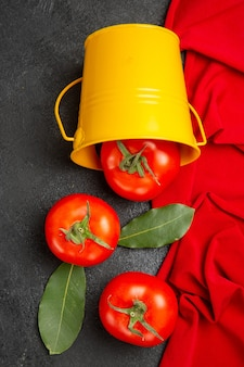 Balde de vista superior com tomate vermelho toalha vermelha em fundo escuro