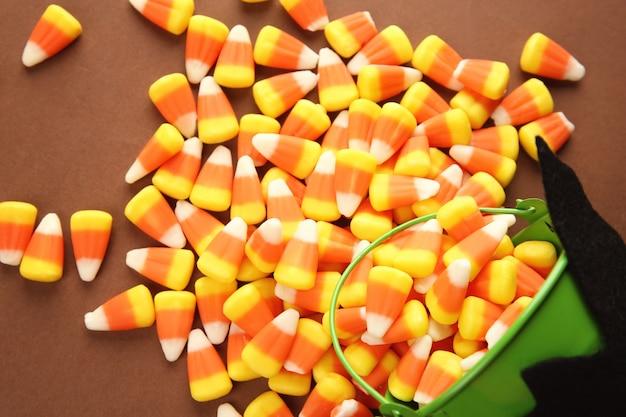 Balde e saborosos doces de halloween na superfície colorida