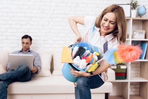 Balde pesado com detergentes nas mãos da mulher.