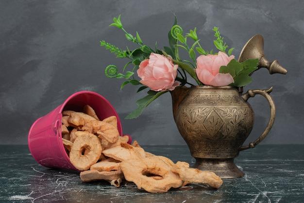 Balde rosa com maçã seca e vaso de flores na mesa de mármore