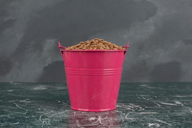 Balde rosa com trigo na superfície de mármore