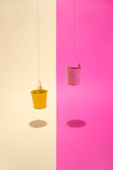 Balde rosa e amarelo em uma parede colorida