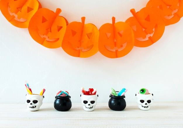 Baldes com doces perto da guirlanda de halloween