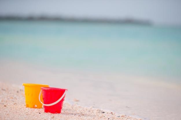 Baldes de plástico na praia de areia branca, beira-mar