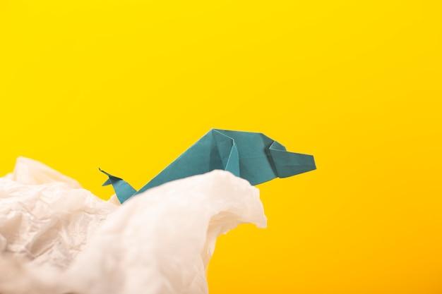 Baleia em uma onda artesanal origami artesanato papel arte em um fundo de papel amarelo