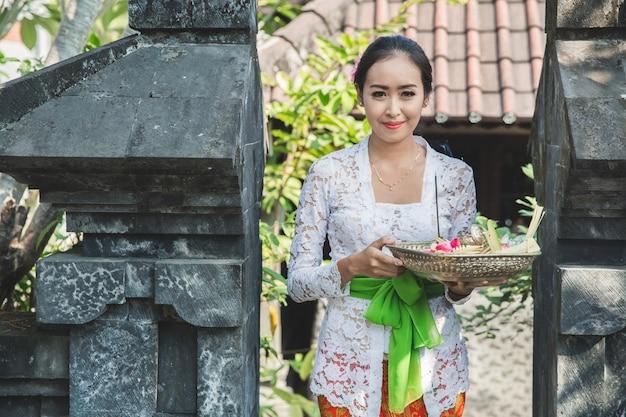 Bali mulher vestindo roupas tradicionais, trazendo sang canang