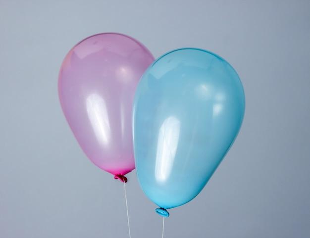 Balões azuis e rosa em cinza.