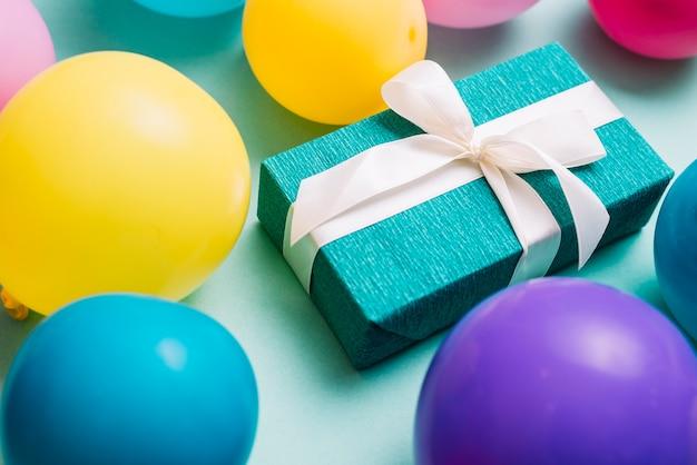 Balões coloridos ao redor da caixa de presente amarrada com fita branca