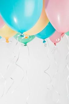 Balões coloridos com fitas em fundo cinza