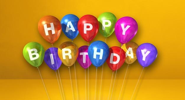 Balões coloridos de feliz aniversário em uma cena de superfície amarela