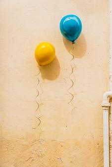 Balões coloridos, decorando uma parede de cor pastel