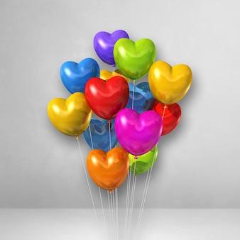 Balões coloridos em forma de coração agrupados em uma superfície branca