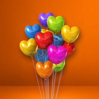 Balões coloridos em forma de coração agrupados na parede laranja