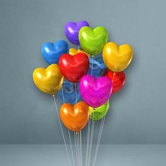 Balões coloridos em forma de coração amontoados em uma parede cinza