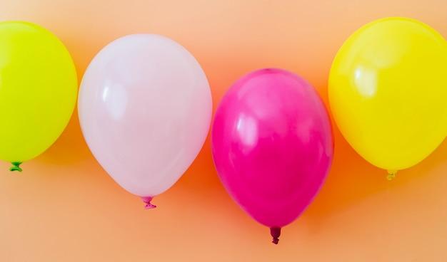 Balões coloridos em fundo laranja
