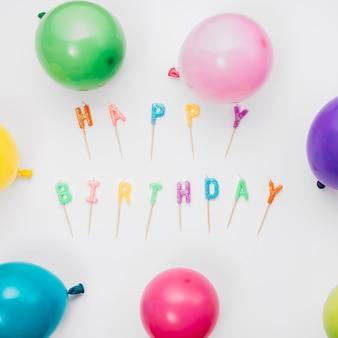 Balões coloridos em torno das velas de feliz aniversário isoladas no fundo branco