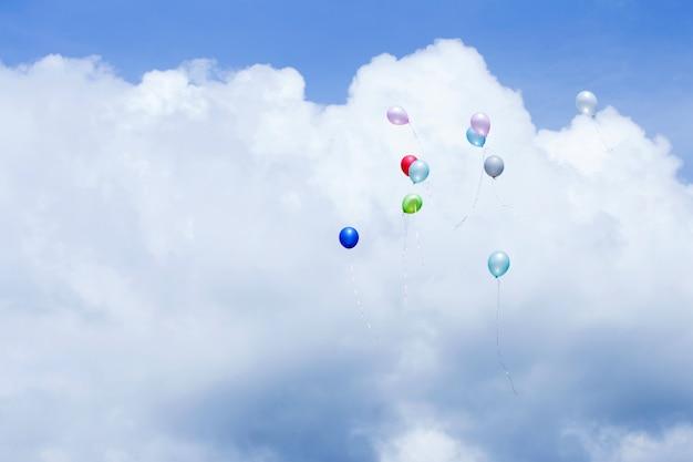 Balões coloridos em um céu azul com nuvens.